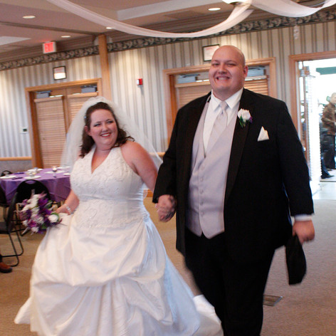 A couple walk in bliss as they enter a reception hall