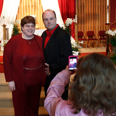 A young girl takes a photo of a couple at a wedding