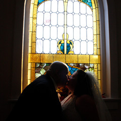 A couple kiss under stained glass