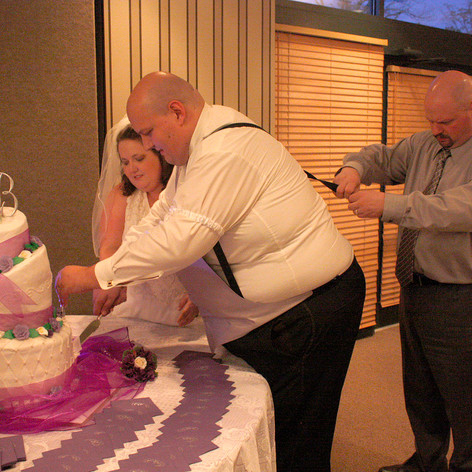Father of the groom fixes a loose strap while the couple cuts the cake