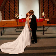 A bride and groom share a kiss after their wedding