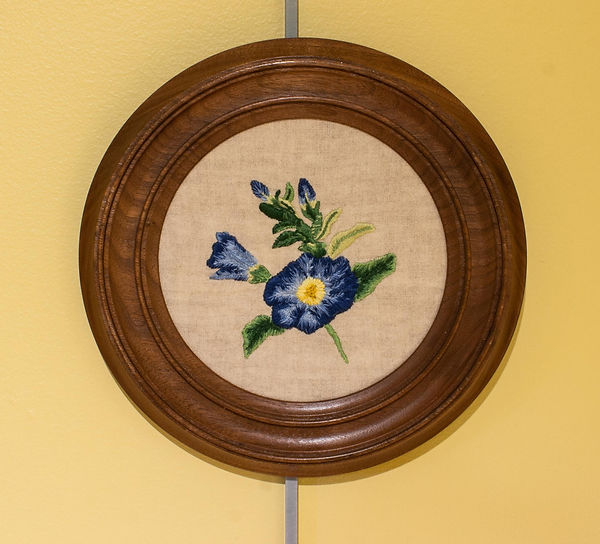 Photograph of an embroidered wall hanging on display in the exhibit. It is circular in shape and features a design of a light and dark blue flower with light and dark green leaves, a short stem and a partially opened secondary flower with additional buds and leaves. The floral design is stitched on an unbleached fabric background and framed in a circular wooden frame.