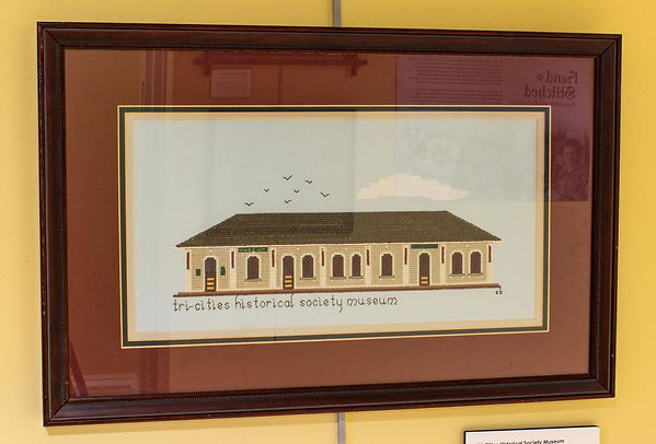 "Photograph of an embroidered wall hanging on display in the exhibit. The piece is stitched on a wide, rectangular piece of stiff blue fabric. An image of the old train depot building that served as the site for the Tri-Cities Historical Museum is cross-stitched on the blue fabric. It is a short but wide building, one story tall. The side of the building is tan-colored to represent the tan bricks. There are three entryways with round, arched doors. There are seven windows with similarly arched openings. The roof is dark-colored and shaped like a trapezoid. A white cloud is stitched above the right side of the building and a group of seven small birds appears to be flying above the left side of the building. Below the building on the left side is stitched, ""Tri-Cities Historical Society Museum,"" and below the right side are the initials, ""SB."" The piece is framed by a maroon-colored mat within a dark wooden frame."