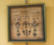 "Photograph of a sampler on display in the exhibit. The sampler is square in shape and framed in a gold and blue wooden frame. The fabric of the sampler is unbleached, woven linen that has become stained and discolored in patches over time. The color of the thread used to stitch the sampler has faded over time and appears to be primarily blue and off-white. But there are areas that suggest some of the thread used to be red. The bottom half of the sampler is taken up with floral designs, and the top has stitched letters. The first line of letters appears to be a lower case alphabet. The second line is a string of upper case letters. Some letters are unintelligible, but that which is legible reads, ""NSBOUDS21AAR."" The third line is an alphabet in upper case letters. A smaller, fourth line reads, ""I 678910,"" and has stitched crowns on either side. Notably, there is no letter ""j"" in either of the alphabets."