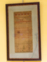 "Photograph of a sampler on display in the exhibit. The sampler is a long, thin, rectangular shape, 7.5 inches wide, 17 inches tall. It is framed with a light blue silk matboard border about 2 inches wide all around and a dark wooden frame. The sampler is stitched on an unbleached open-weaved fabric that has turned brown over time. It has stitched lines in different patterns and colors at the top. Then an alphabet stiched followed by numbers 1-14. The first line of text after the numbers is indecipherable because the thread has faded. Continuing down is a block of text stitched in red, white and green that reads, ""Let me O God my / Labor SoemPly tha/ I a ComPetency may/ enjoy I ask no more than my life S wants / SuPPly and leave W / Their due mothers / when I die / ...is 1824 / Jane Corlett Workt"" [sic]. At the bottom is a design of trees and flowers with birds. In between the trees and flowers are the initials ""JC."""