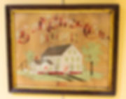 "Photograph of an embroidered wall hanging on display in the exhibit. The piece is 19 inches wide by 15 inches tall. The background is brown perforated cardboard. The phrase, ""God Bless Our Home"" is stitched in a gothic-style script in variegated red to white thread. Below the motto is an image of a farmhouse that is white with a dark-colored roof. Upon closer inspection, the roof has not been stitched and is the original printed design on the cardboard. Windows are stitched in a light blue, and the grass is green with two trees, two dark-colored pathways leading from the house, and a well in the back. Below the house, the artist stitched the date, 1880. The piece is framed in a wooden frame."