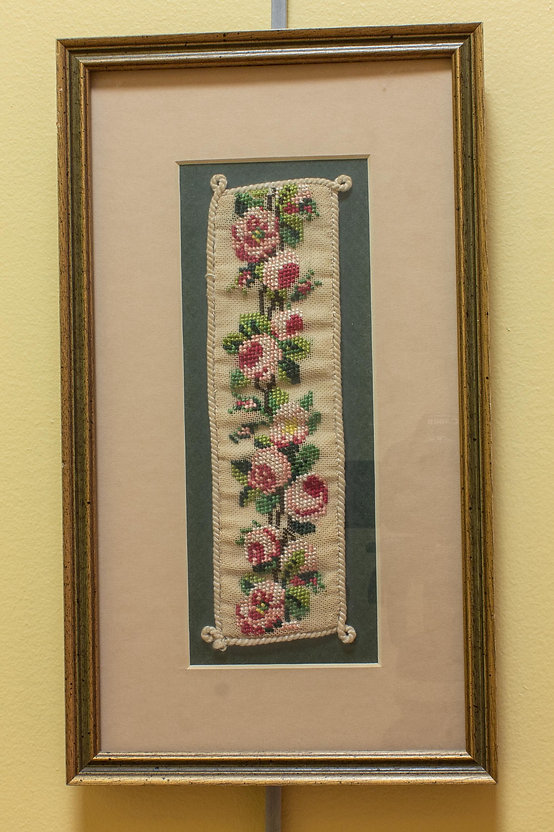 Photograph of a piece of embroidery on display in the exhibit. It appears to be an embroidered bookmark in a frame. The bookmark is a long and narrow strip of off-white fabric on which is an embroidered design of pink flowers and green leaves. There is a stitched white border around the edge with small loops on each corner. The bookmark is framed against a blue background with a light-colored mat border about 2 inches around. The whole piece is framed in a wooden frame.