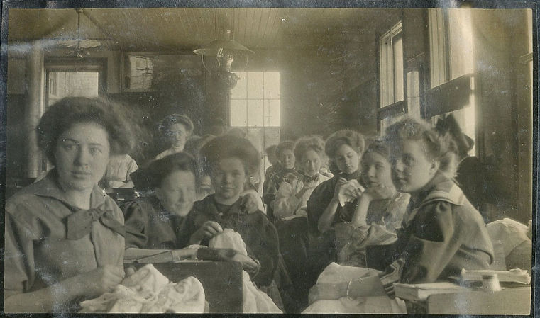 "A black and white historical photograph that was taken around the year 1907. The image shows the interior of a classroom in the old Akeley Institute in Grand Haven. There is sunlight streaming through four windows. There are approximately 12 young girls of various ages seated throughout the room. They are seated at desks very close together and appear relaxed. They are all in the midst of a sewing class and are holding their projects (fabric and needles) in their hands. They are dressed in early 1900s daytime clothing of middling quality and fashion. Their hair is up in a fashionable ""Gibson girl"" style, some with large bows."