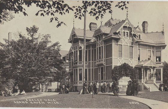 "Black and white historical photograph of Akeley Hall in Grand Haven taken around 1920. There are small groups of girls milling around in the yard in front of the building dressed in what is likely school uniforms with long skirts and blouses with sailor-style bibs. The building is in the highly decorative Victorian style with ""gingerbread"" wooden trim around the eaves, windows, and doors. The wooden trim is painted in different colors. The exact colors are not clear since the image is in black and white."
