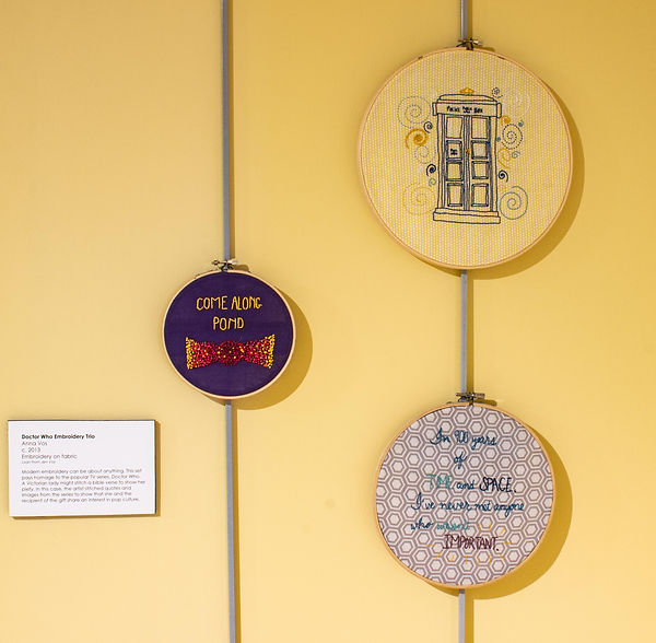 "Photograph of a three embroidered wall hanging on display in the exhibit. They are framed in three different sized wooden embroidery hoops. The largest piece is stitched on a background of a fabric with a yellow geometric pattern on a white background with a stitched design of a blue ""police box"" that is a type of phone booth. The police box has two tall and thin paneled doors, a base and a top that says ""Police Public Call Box."" Stitched around the police call box are swirls of different colors. The middle-sized embroidery piece is stitched on fabric that is a gray geometric pattern on a white background with a stitched design quote that reads, ""In 900 years of time and space, I've never met anyone who wasn't important."" The words are stitched in different colors and the words ""TIME, SPACE, and IMPORTANT"" are emphasized in all capital letters. The smallest embroidery piece is stitched on a solid, navy blue background and features the text, ""COME ALONG POND,"" and a design of a bowtie."