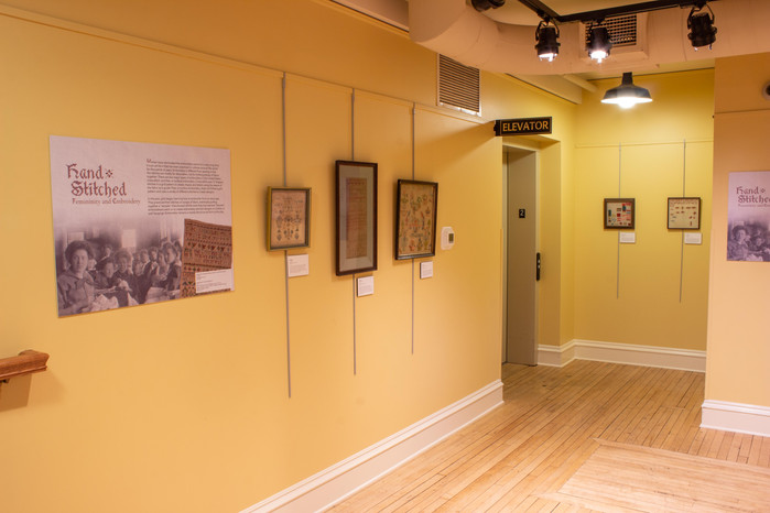 Photograph of the Hand Stitched exhibit displayed in the Mezzanine of the Tri-Cities Historical Museum. The view looks towards the wall opposite the public bathrooms. Visible is the third panel and four wall hangings. There is a trio of embroidery pieces in circular embroidery hoops to the left of the panel. A small, circular embroidery piece hung between two larger rectangular embroidery pieces on the wall to the right of the text panel.  Each embroidery piece is described in more detail later in this exhibit.