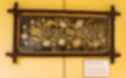 "Photograph of a piece of embroidery on display in the exhibit. The piece is a long, horizontal rectangular wall hanging. The background is black perforated cardboard, and it is stitched with the phrase ""Scatter Smiles"" in elaborate gothic-style letters surrounded by flowers. The design is stitched in what appears to be a color palette of whites, golds, and light browns. It is possible that some of the thread has faded over time. The piece is framed with a dark, wooden frame."