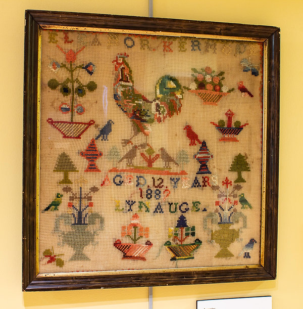 "Photograph of a sampler on display in the exhibit. The sampler is nearly square in shape, framed in a dark wooden frame. The sampler is 16 inches wide and 16.5 inches tall. At the top of the sampler is stitched the name, ""Eleanor Kermode"" in all capital letters, each letter in a different color. Below her name, Eleanor stitched different designs of flowers in baskets and planters. The largest design is of a multi-colored rooster. Below the rooster are two small birds that face each other with a small flower between them. The floral designs are similar to the sampler stitched by Eleanor's relative, Jane Corlett, 60 years before. Below the birds, Eleanor stitched, ""aged 12 years / 1882 / Lynauge."" The 2 in 1882 is missing the bottom line, but 1882 best fits the established timeline of Eleanor's life. Below the text are additional stitched flowers in planter designs. Overall the sampler is made with colorful wool thread on a wide weave fabric."