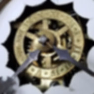 Close up photograph of the brass alarm mechanism. It is a wheel that is situated in the center of the primary clock face. Around the circular edge of the wheel are the roman numerals 1-12 where the user can set the time for the alarm. The wheel is connected to the center by six spokes. Visible behind the wheel are gears and mechanisms for running the clock.