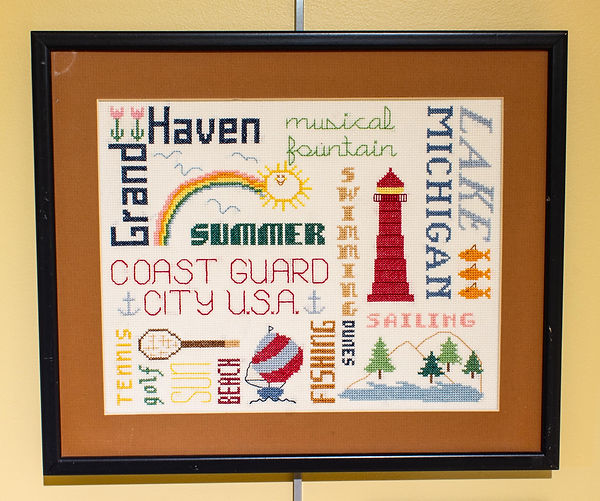 "Photograph of an embroidered wall hanging on display in the exhibit. The piece is a cross-stitched design of words related to Grand Haven in different colors and fonts with the words fitting together both horizontally and vertically, forming a geometric grid pattern. The words featured in the piece roughly from top to bottom, left to right are, ""Grand Haven / musical fountain / Lake Michigan / summer / swimming / Coast Guard City USA / tennis / golf / sun / beach / fishing / dunes / sailing."" There are images of a rainbow, sun, lighthouse, fish, tennis racket, sailboat, and dunes with trees cross-stitched in between the words."