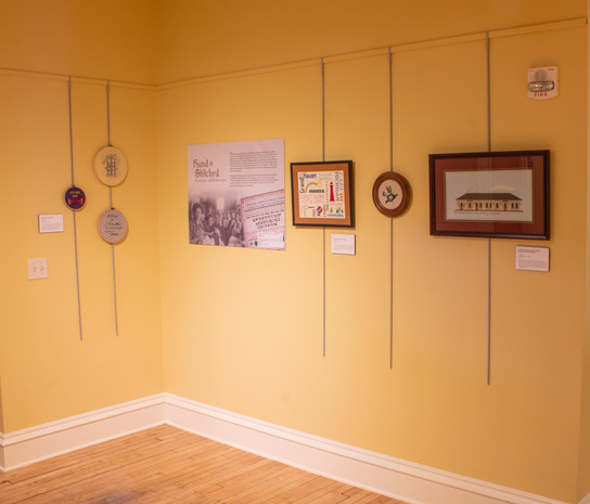 Photograph of the Hand Stitched exhibit displayed in the Mezzanine of the Tri-Cities Historical Museum. The view looks towards the elevator from the entrance to the West Michigan Pike exhibit with the first text panel and five embroidery samplers hung on yellow walls. Each embroidery piece is described in more detail later in this exhibit.