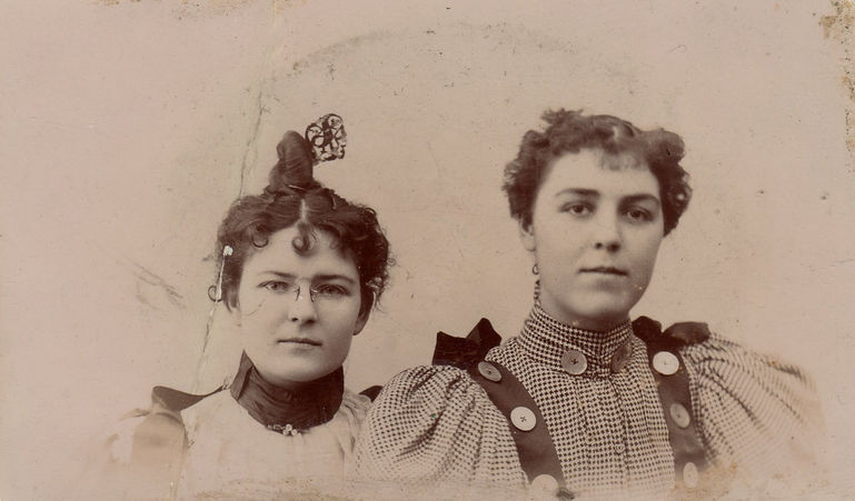 A historical black and white photograph taken around the 1890s, judging from the hair and clothing style of the subjects. Two young women sit close together, the young woman on the right is arranged slightly in front of the young woman to the left with their shoulders overlapping. They're expressions are relaxed, and they are not smiling (common in the 1800s) They are dressed in 1890s style dresses with poofy sleeves and high collars around their necks. The woman on the left is Cora Barnett Plumley. Her clothes and hair are more elaborate than the woman to the right (Eleanor Kermode). Eleanor's style is fashionable but simple.