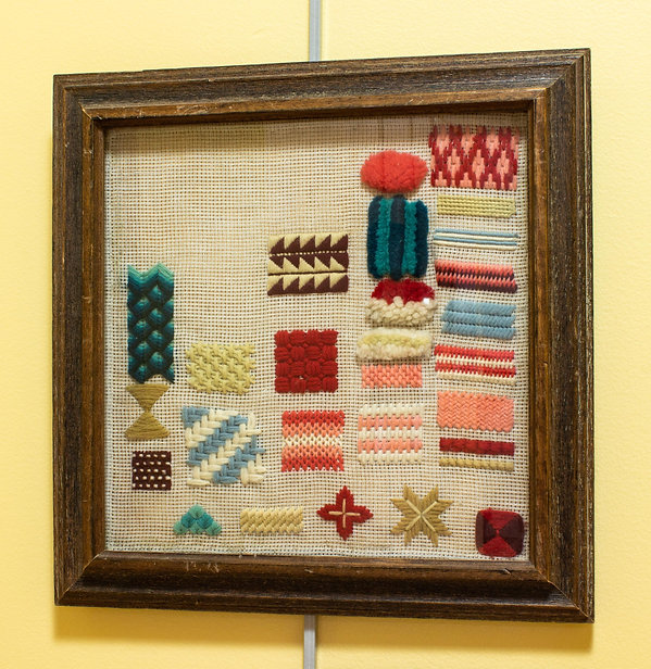 Photograph of a pattern sampler on display in the exhibit. Unlike the other samplers, this one does not have any letters, numbers, or alphabets stitched on it. The square-shaped sampler has small rectangular swatches of different patterns stitched on it. The patterns are stitched in colorful, wool thread. The patterns include stripes, herringbone, diamonds, and triangles.