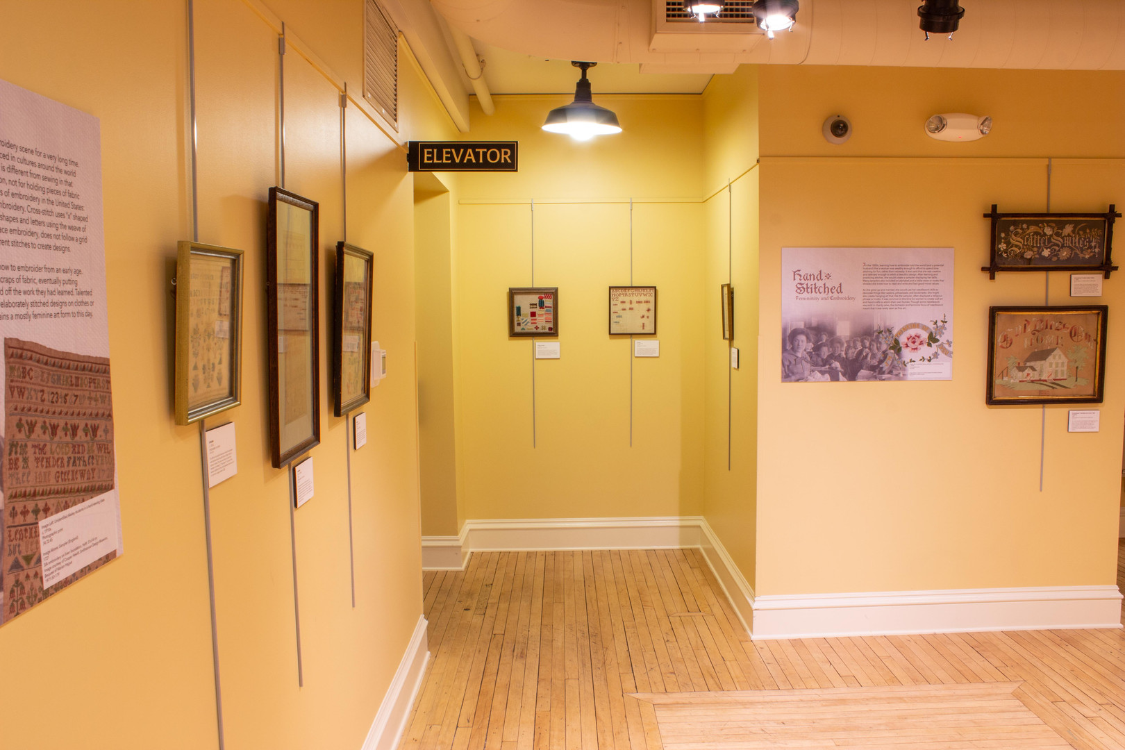 "Photograph of the Hand Stitched exhibit displayed in the Mezzanine of the Tri-Cities Historical Museum. The view looks towards the elevator from the top of the stairs. Visible are two embroidery samplers on the far wall by the elevator as well as the second panel and two embroidered wall hangings on the wall of the men's bathroom. The wall hangings are hung stacked vertically. The one on top reads, ""Scatter Smiles"" and the bottom reads, ""God Bless Our Home.""  Each embroidery piece is described in more detail later in this exhibit."