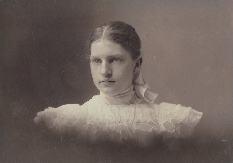 A black and white historical studio portrait photograph of Henrietta Kiel taken around 1905. Her head and shoulders are visible against a plain, dark backdrop. She is wearing a white dress with a high collar. There are several layers of flounces across the bodice and shoulders. Henrietta looks slightly off to the left of the camera and has a relaxed but unsmiling expression on her face. She wears no makeup (as is typical of the fashion at this time) and her straight, blond hair is parted in the center and pulled back and fastened at the nape of her neck with a white hair bow.