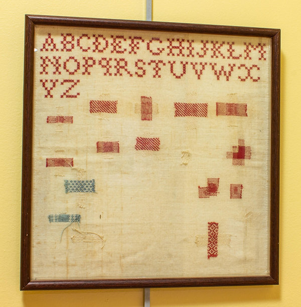 Photograph of an embroidery sampler on display in the exhibit. This square-shaped sampler is simple in design. It consists of a cross-stitched alphabet in capital letters stitched in red thread. Below the alphabet are swatches of different patterns scattered irregularly over the surface of the unbleached woven cloth. The pattern swatches are mostly stitched in red and white thread, but there are two swatches stitched in blue and white thread on the lower left side of the sampler.