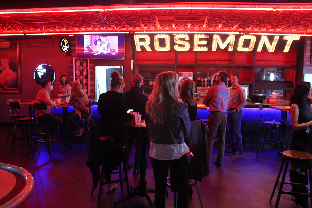 A small, masked group of people stand at Rosemont Bar to watch Kids with Cancer Got Talent. A television shows a life feed, and red LED lighting lines the ceiling
