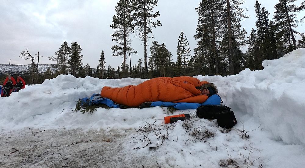 Winter camper sleeping in big sleeping bag in snow