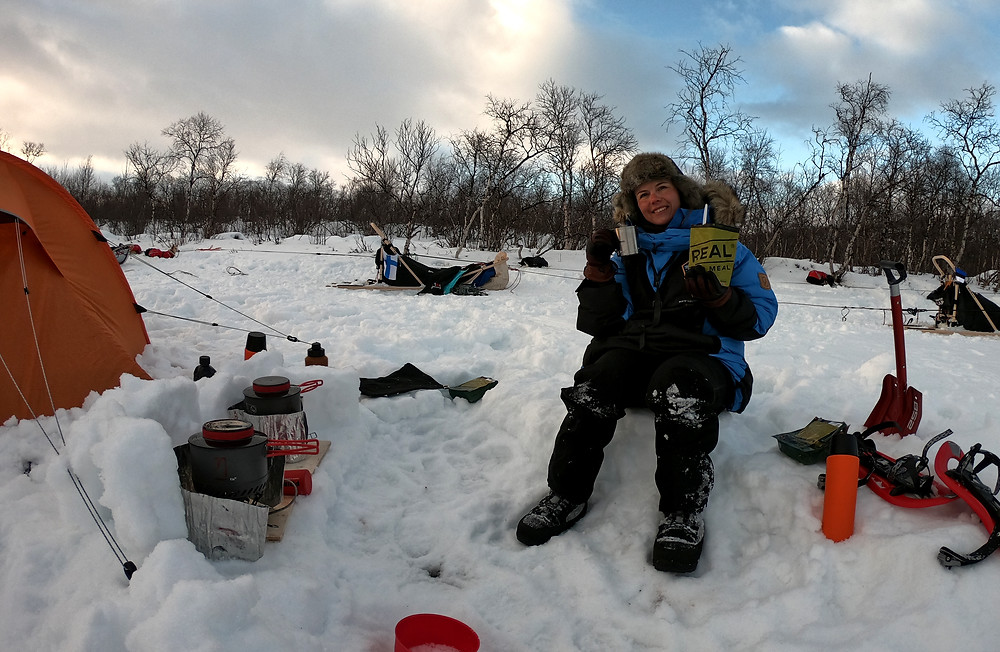 Woman sitting in snow, in winter camp, eating camp food.