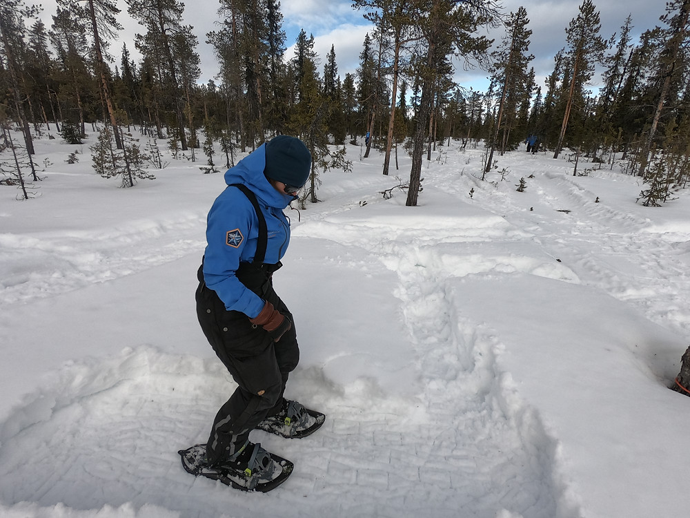 Woman in snowshoes stamping down snow in winter camp.