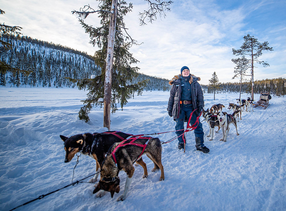 Sled dog musher standing with her dogs in snow landscape.