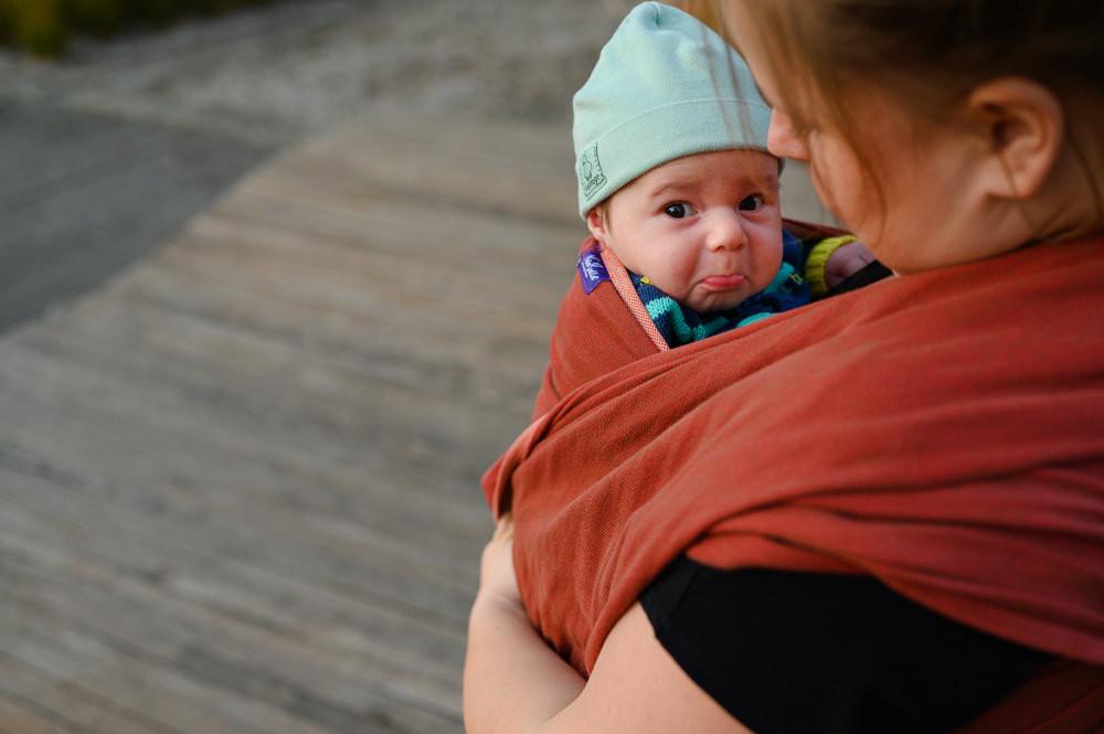 Portrét kojence v šátku při venkovním rodinném focení.