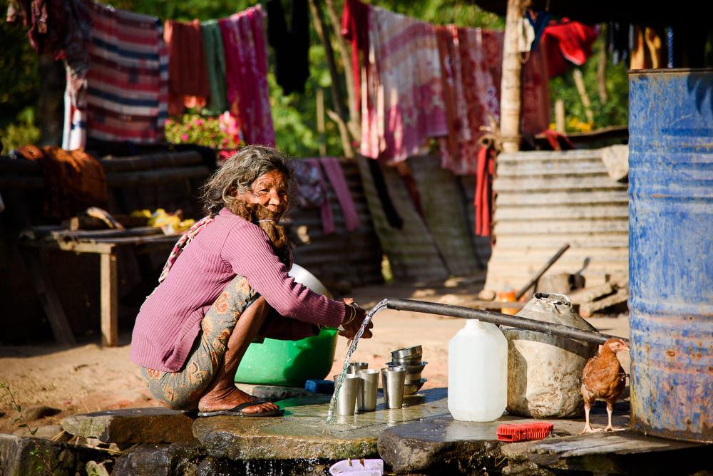 Žena myje nádobí vodou z barelu v nepálské vesnici u Pokhary.