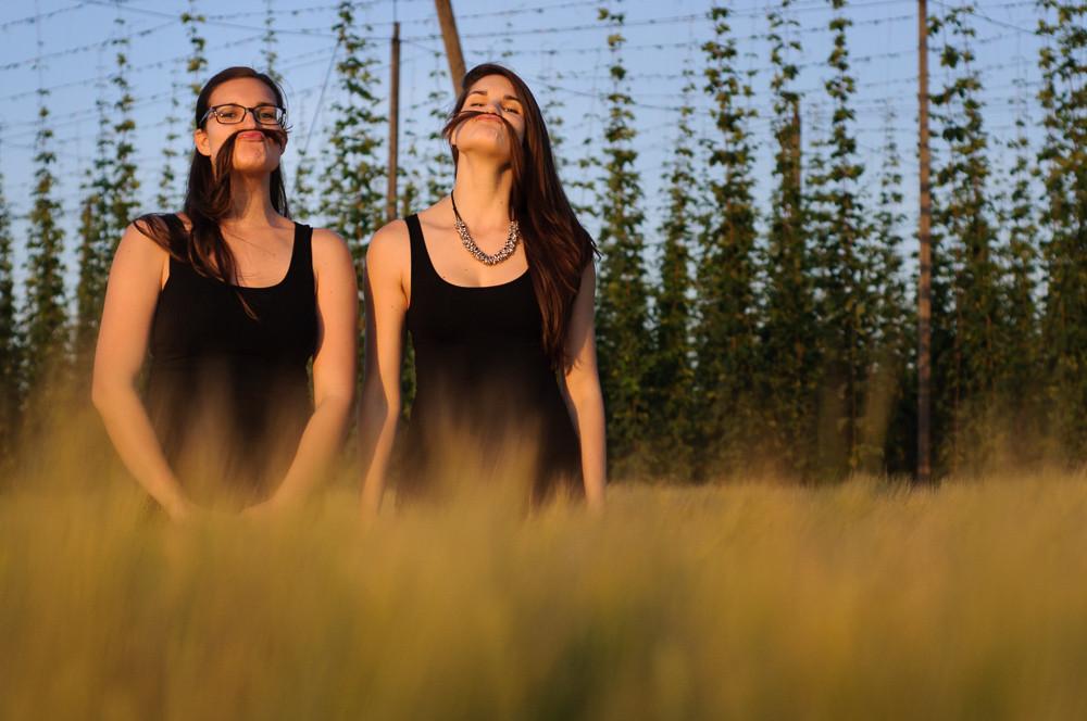 Sestry pózují s knírky z vlasů při focení v poli při západu slunce.