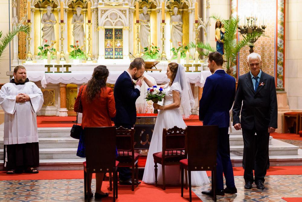 Ženich po předání nevěsty líbá její ruku před oltářem při obřadu, katedrála svatého Václava v Olomouci.