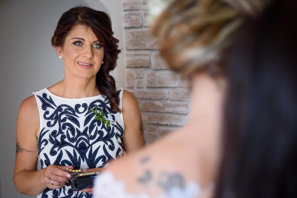 Maminka nevěsty při pohledu na dceru ve svatebních šatech