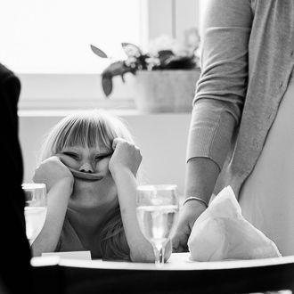 Dítě družička sedí u stolu a nudí se při proslovu svědka.