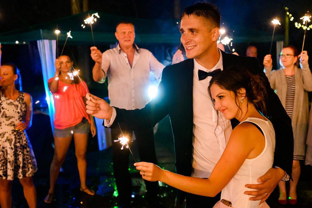 Novomanželé a svatební prskavky při večerním focení po dešti.