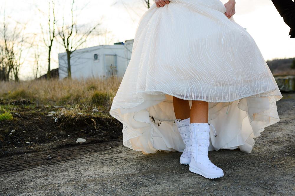 Nevěsta ukazuje zimní boty pod šaty pro zimní svatbu.