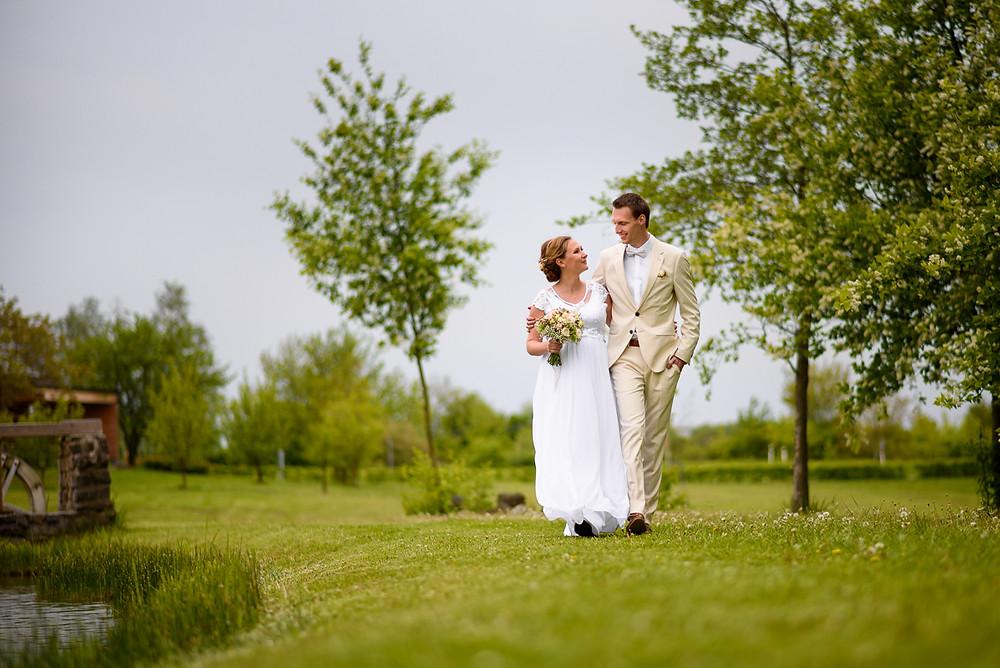 Ženich v bílém obleku ladícím s nevěstou jdou kolem rybníka Prachárna.