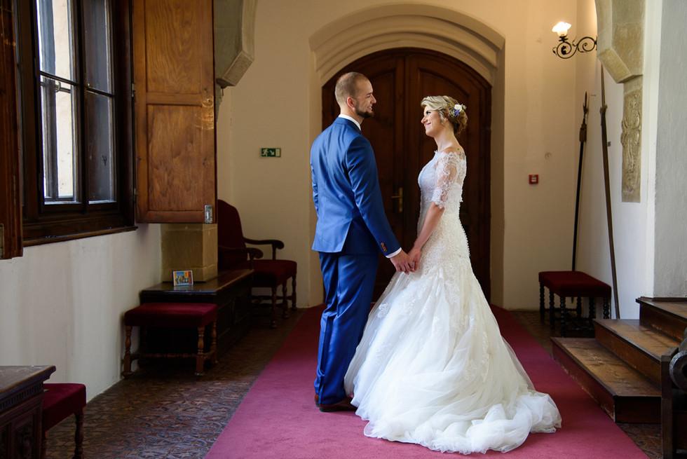 Ženich s nevěstou sdílí moment po focení před odchodem z hradu