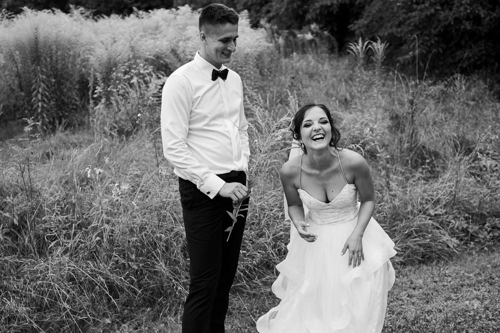 Nevěsta se smíchem při zábavném svatebním fotografování venku na louce.