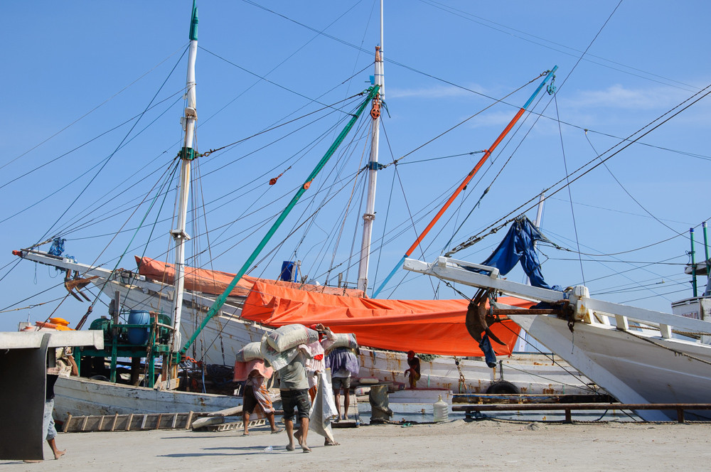 Men are loading a boat with bags in Port Paotere, Makassar, South Sulawesi, Indonesia.