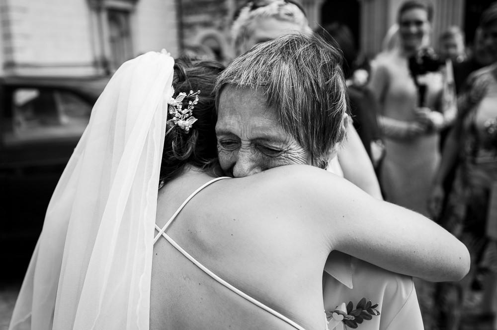 Nevěsta objímá babičku při emotivní gratulaci po obřadu.