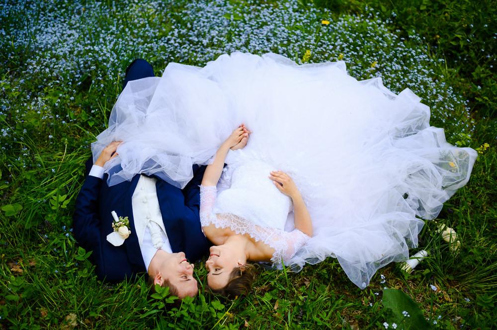 Nevěsta s ženichem leží v trávě při portrétním svatebním focení.