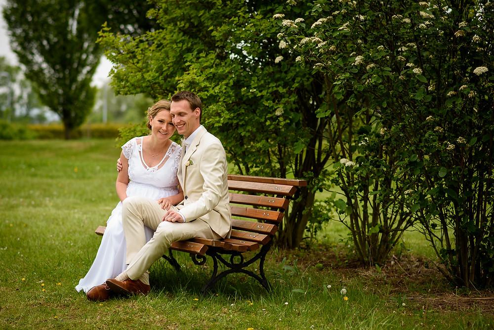 Ženich s nevěstou na lavičce při portrétním focení.