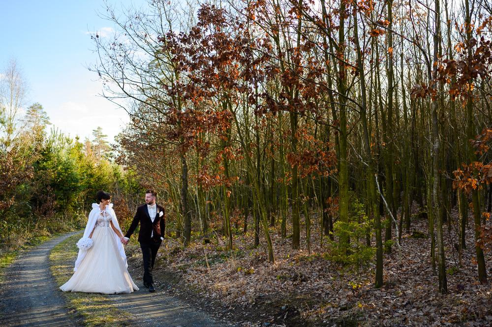 Ženich s nevěstou jdou bok po boku při zimním svatebním focení.