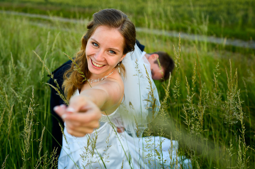 Ženich nevěsty zapíná šaty v trávě.