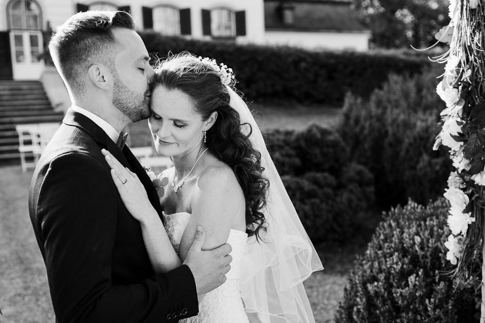 Ženich dává nevěstě pusu na čelo pod slavobránou po obřadu v Náměšti na Hané.