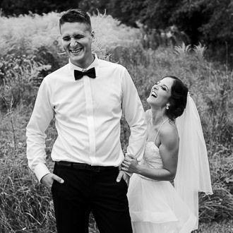 Nevěsta lechtá ženica trávou při zábavném venkovním focení na svatbě.