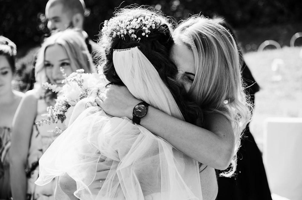 Družička objímá nevěstu při dojemné gratulaci po obřadu.